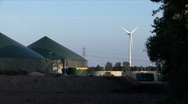 Windmill next to biogas installation Stock Footage