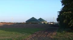 windmill next to biogas installation - wider - stock footage