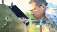 Man preparing grill, outdoors, steadicam shot HD Stock Footage