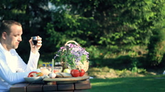 Happy man drinking wine by the table full of food, outdoors, dolly shot HD - stock footage
