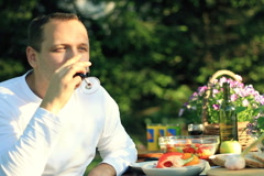 Happy man eating and drinking wine by the table, outdoors NTSC Stock Footage