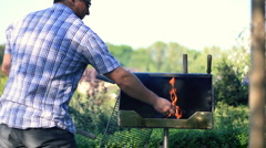 Man preparing grill, outdoors, dolly shot HD Stock Footage