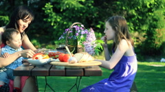 Mother with children eating in the garden, dolly shot HD - stock footage
