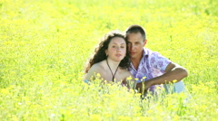 Stock Video Footage of Young love couple sitting in flowers. Tripod pan.