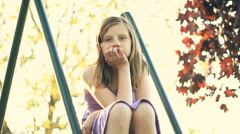 Sad teen girl sitting in the park, sunny day HD Stock Footage