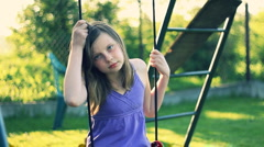 Stock Video Footage of Sad teen girl sitting on the swing in the garden HD