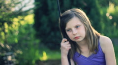 Sad teen girl sitting on the swing in the garden, dolly shot HD Stock Footage