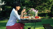 Pensive woman drinking wine by the table full of food, outdoors, dolly shot Stock Footage