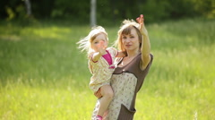 Happy mother and child waving his hand in the park - stock footage