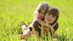 Happy family in the grass look at camera Stock Footage