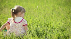 Offended by a little girl looks at camera. In the grass. Stock Footage