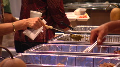 CU peoples hands serving themselves food from trays Stock Footage