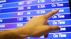 Hand and finger scanning and looking for flight information at airport monitor. Stock Footage