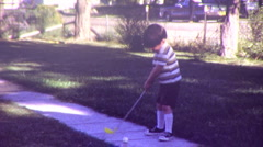 CUTE LITTLE BOY Plays Golfing on Lawn Golf 1970s (Vintage Film Retro Home Movie) Stock Footage