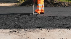 Road construction workers leveling asphalt using shovel and rake - Timelapse Stock Footage