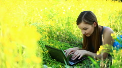 Young lady with laptop in the grass. Tripod pan. Stock Footage