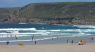 Stock Video Footage of Wide sandy beach and surfers at Sennen Cove Cornwall