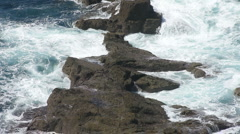 Waves crash onto rocks at Lands End Cornwall Stock Footage