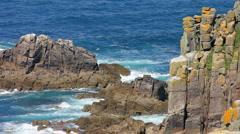 Waves crash onto rocks at Lands End Cornwall - stock footage