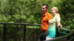 Couple leaning on railing, talking Stock Footage