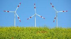 Windmills behind rape field Stock Footage