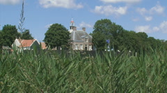 Schokland World heritage: Church and wooden seawall behind reed land in polder Stock Footage