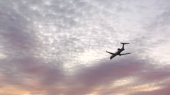 Plane Flying into City at Sunset Stock Footage