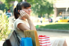 Shopping woman sitting on bank after shopping and talking on the phone Stock Footage