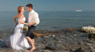 Bride and groom kissing on beach Stock Footage