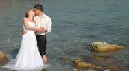 Bride and groom kissing near the sea Stock Footage