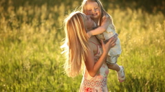 Happy mother playing with baby on the meadow Stock Footage