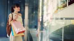 Attractive woman with shopping bags looking at shop window HD - stock footage