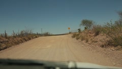 Riding down dirt road as seen through front window of vehicle Stock Footage