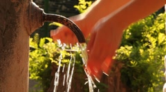 Woman washes hands in stream of water from old rusty tap Stock Footage