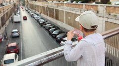 Boy in checkered shirt stand on foot bridge and blow bubbles over road Stock Footage