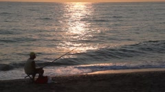Man fishes and observes of sunset while sitting on coast Stock Footage