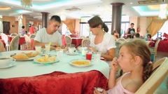 Family from three persons has breakfast in dining room Hotel Club Bellerive Stock Footage