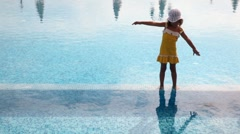 Girl stands in water in pool and with the lifted hands bends to right and to Stock Footage