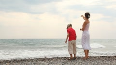 Mother and son stand on sea coast and throw pebbles Stock Footage
