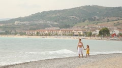 Mother with daughter walk keeping for hands on sea coast Stock Footage