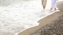 Male and female feet walk on coast Stock Footage