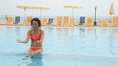 Woman sits in pool shallow water in front of chaise longue and beach umbrella Stock Footage