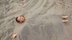 Boy lies smiles buried up with sand on beach Stock Footage