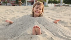Little girl smiles siting filled up with sand on neck on beach Stock Footage