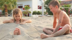 Playing elder brother falls up with sand his sister tries stand up Stock Footage