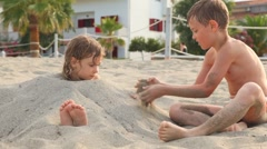 Playing elder brother falls up sister with sand - stock footage