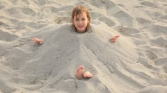 Little girl sits filled up with sand on neck on beach Stock Footage