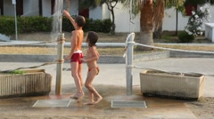 Elder brother with sister rinse under shower on beach - stock footage