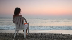Woman sits on plastic chair alone on beach faced to sea Stock Footage