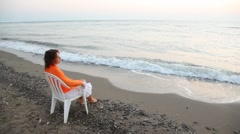 Woman sits on chair alone on beach and looks in distance pensive Stock Footage